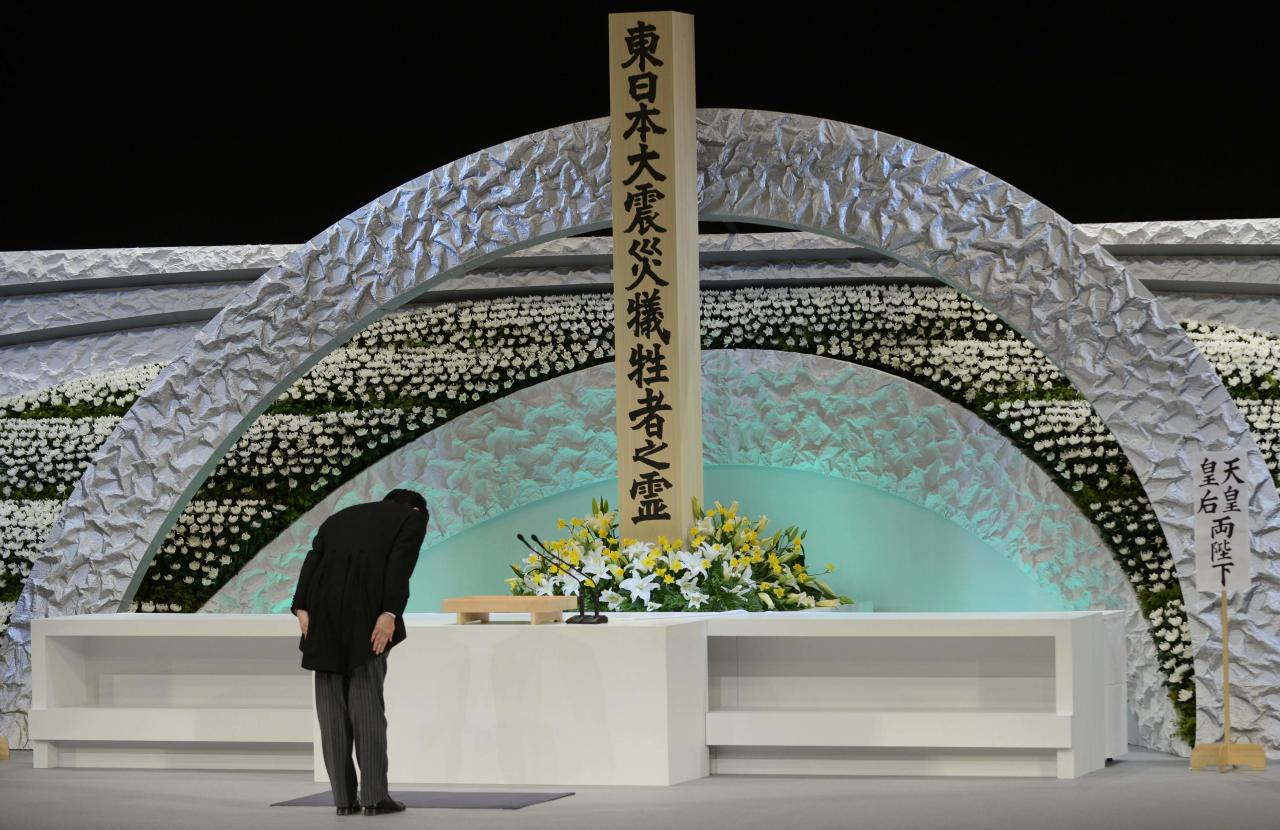 Japan's Prime Minister Shinzo Abe bows in front of the altar for the victims of the March 11, 2011 earthquake and tsunami at the national memorial service in Tokyo March 11, 2014. Tuesday marks the third-year anniversary of the March 11, 2011 earthquake and tsunami that killed thousands and set off a nuclear crisis. REUTERS/Franck Robichon/Pool (JAPAN - Tags: ANNIVERSARY DISASTER POLITICS)