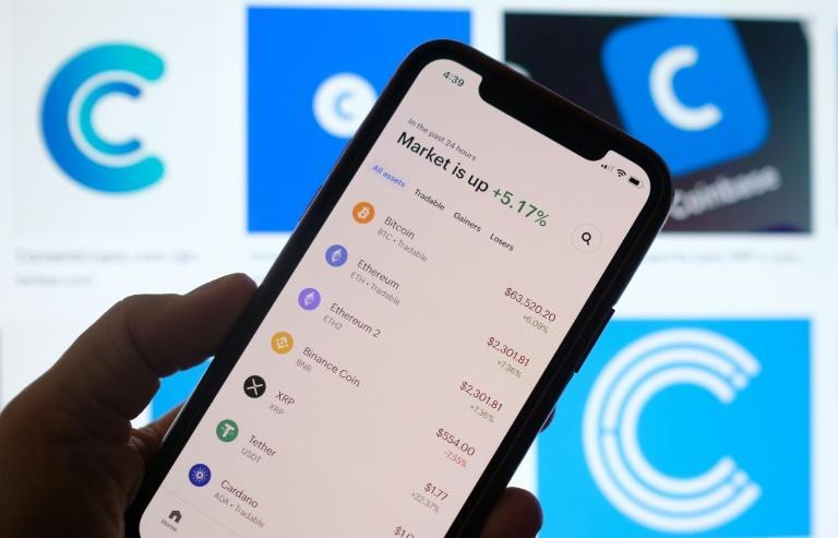 This illustration photo shows the Coinbase logo in the background as a person checks cryptocurrencies prizes on a smartphone in Los Angeles on April 13, 2021