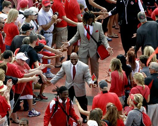 Louisville coach Charlie Strong, center, joins players to greet fans during the pre-game Cardinal March to the stadium before an NCAA college football game against Missouri State in Louisville, Ky., Saturday, Sept. 8, 2012. (AP Photo/Garry Jones)