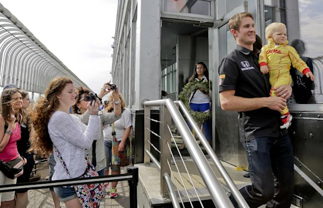 Tourists at the top of the Empire State Building snap photos of Indianapolis 500 winner Ryan Hunter-Reay and his son, Ryan, as he arrives for a photo shoot and interviews, Tuesday, May 27, 2014, in New York. Hunter-Reay defeated three-time Indy winner Helio Castroneves on Sunday and is the first American to win the race since 2006. (AP Photo/Julie Jacobson)