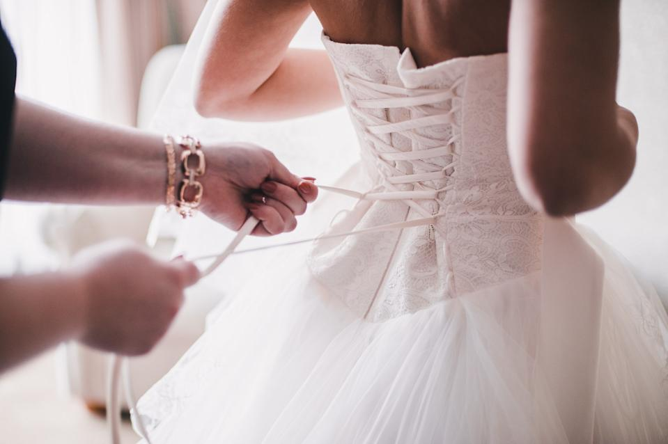 Bridesmaid helping the bride to wear a dress