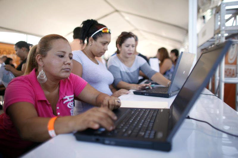In this Sept. 25, 2013 photo, job seeker Wendy Cordova fills out contact forms at a job fair in Catano, Puerto Rico. Cordova, a hair stylist and mother of five who relies mostly on Social Security payments after her husband died in 2005, says she is struggling to pay the medical bills of her teenage daughter who is diabetic. (AP Photo/Ricardo Arduengo)