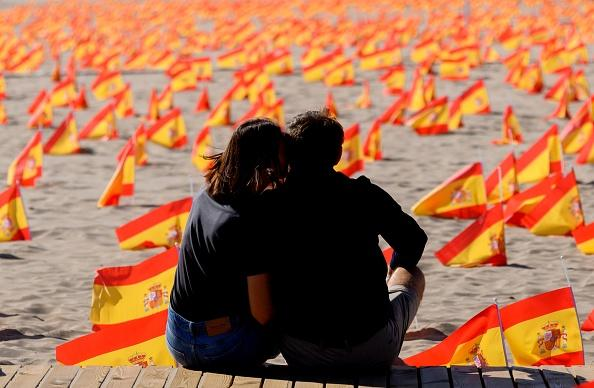 A couple sits close to thousands of Spanish flags, representing the Spanish victims of Covid-19, on Patacona beach in Valencia.