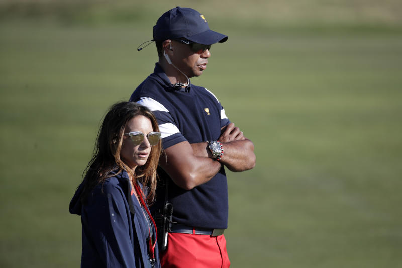 Tiger Woods, top, assistant United States team captain, and his associate Erica Herman, watch play on the 17th hole during the final round of the Presidents Cup golf tournament at Liberty National Golf Club in Jersey City, N.J., Sunday, Oct. 1, 2017. (AP Photo/Julio Cortez)