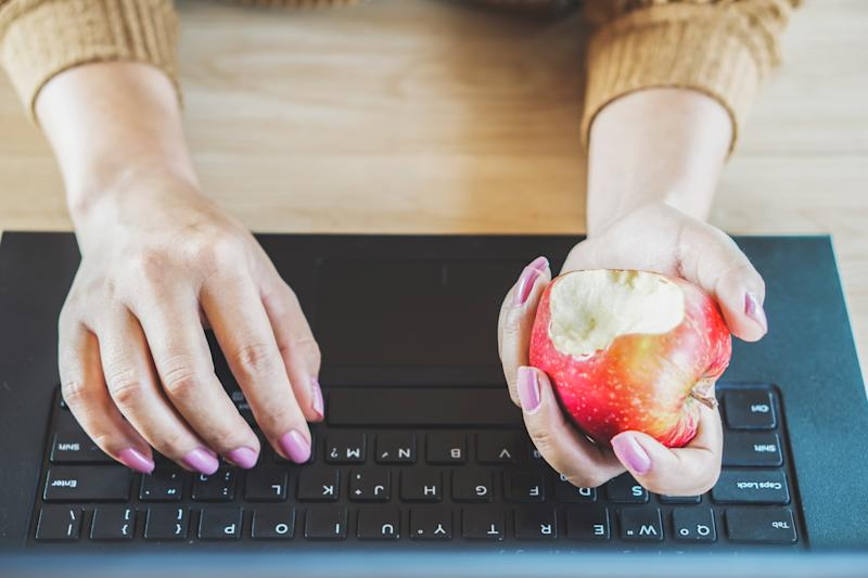 Woman hand working on computer and eating apple at desk for diet
