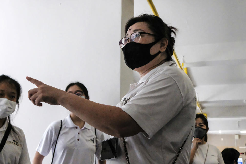 Keeping Hope Alive founder Fion Phua briefs members before their volunteer work Sunday, Oct. 4, 2020 in Singapore. Members of the volunteer group conduct weekend door-to-doorvisits to deliver goods or provide services to people in need. (AP Photo/Ee Ming Toh)