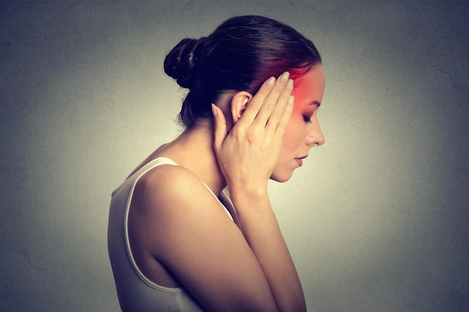 Woman having headache with her head in her hands isolated on gray wall background