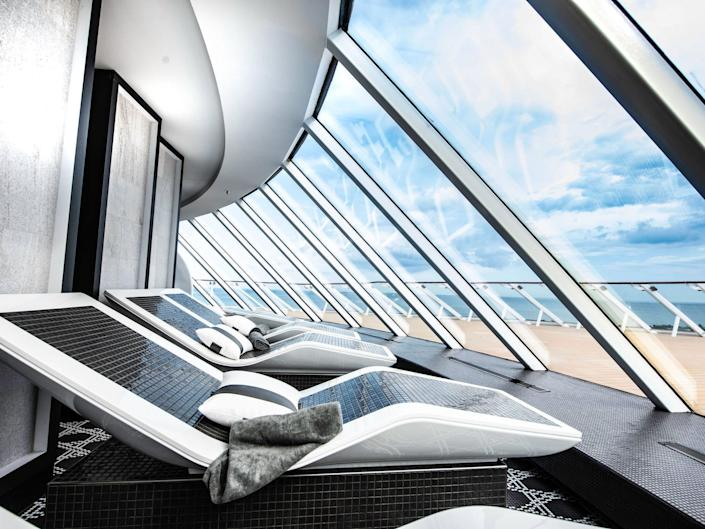 indoor black and white spa chairs overlooking a deck behind glass panels aboard the Celebrity Edge