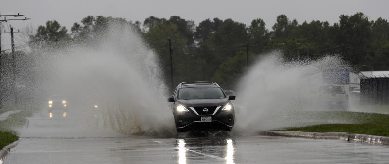 A car drives through floodwaters from Tropical Depression Imelda Wednesday, Sept. 18, 2019, in Houston. (AP Photo/David J. Phillip)