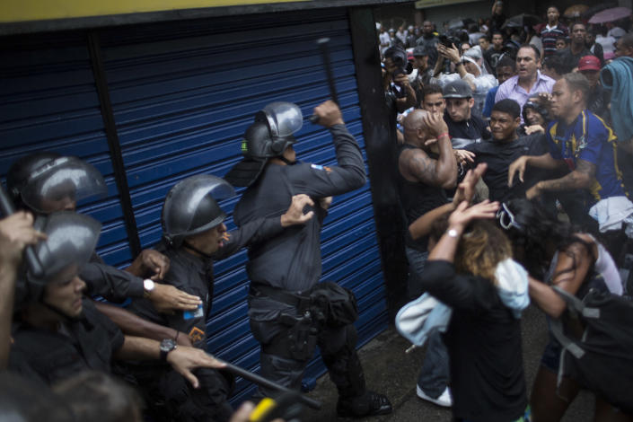 Residents of Pavao Pavaozinho slum clash with riot police during a protest against the death of Douglas Rafael da Silva Pereira, after his burial in Rio de Janeiro, Brazil, Thursday, April 24, 2014. The protest followed the burial of Pereira, whose shooting death sparked clashes Tuesday night between police and residents of the Pavao-Pavaozinho slum. (AP Photo/Felipe Dana)