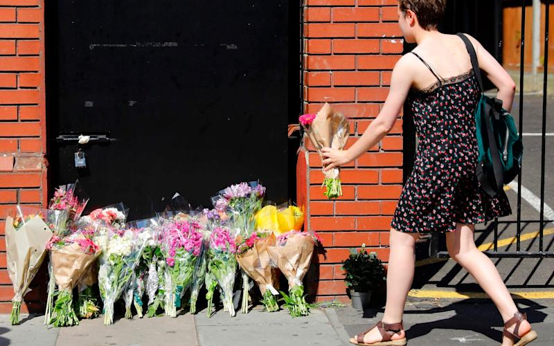 A woman lays flowers in tribute outside Finsbury Park Mosque - Credit: TOLGA AKMEN/AFP