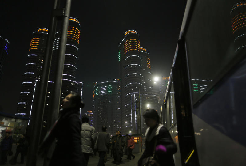 In this Tuesday Feb. 25, 2014 photo, North Koreans get off a bus at a residential complex which is lit at night in Pyongyang, North Korea. (AP Photo/Vincent Yu)