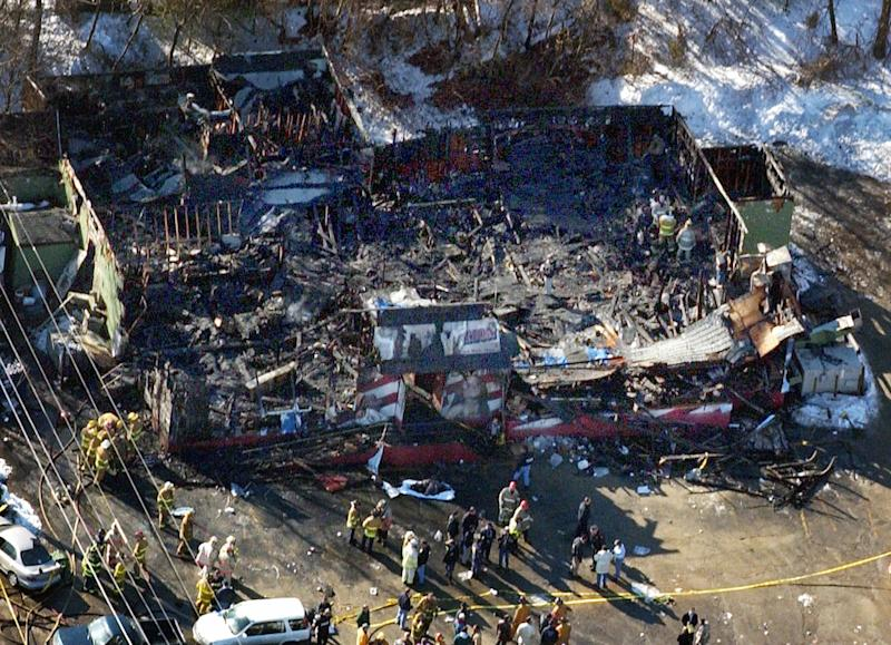 File -- In this Feb. 21, 2003 file photo fire fighters continue to investigate the burned out remains of the Station nightclub in West Warwick, R.I. in this aerial photo. The Station Fire Memorial Foundation, which is working to build a memorial at the site of a nightclub fire, is having trouble raising money for the project which is already underway. The project is estimated to cost $1.4 million and they have less than $200,000 in the bank. The blaze claimed the lives of 100 people. (AP Photo/Robert E. Klein, File)