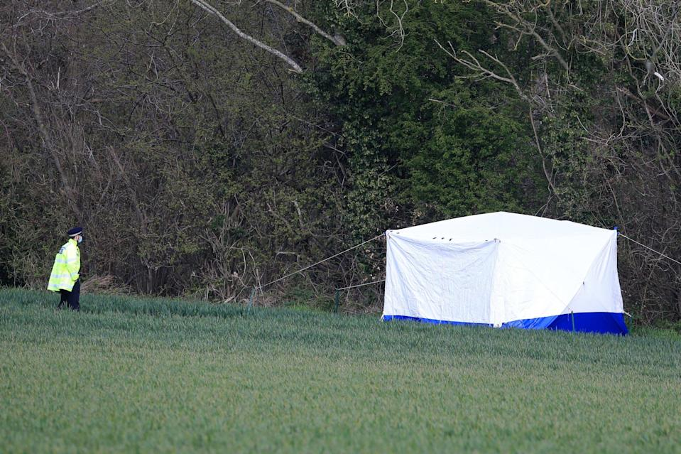 A police officer stands near a forensic tent on the outskirts of Akholt Wood in Snowdown, KentPA