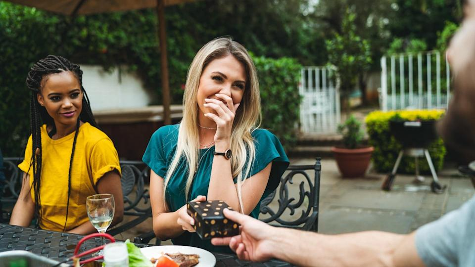 Happy young woman covering mouth while receiving gift by man.
