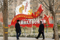"""Residents walk past government propaganda, some of which reads, """"Socialist core values,"""" in Hotan in northwestern China's Xinjiang Uyghur Autonomous Region on March 22, 2021. Four years after Beijing's brutal crackdown on largely Muslim minorities native to Xinjiang, Chinese authorities are dialing back the region's high-tech police state and stepping up tourism. But even as a sense of normality returns, fear remains, hidden but pervasive. (AP Photo/Ng Han Guan)"""