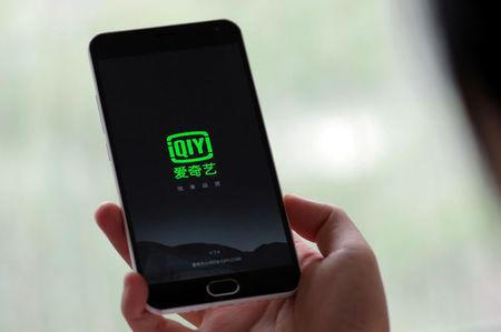 FILE PHOTO: A person holds a phone with Baidu Inc's video streaming service iQiyi in Jinan, Shandong province, China, in this May 25, 2016 photo illustration. REUTERS/Stringer/File Photo