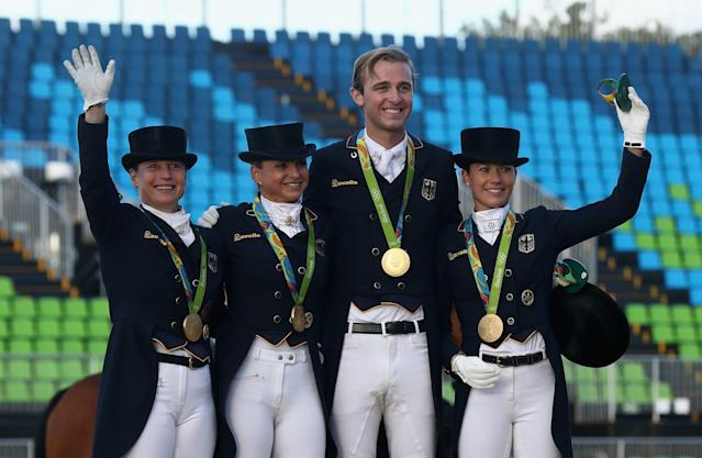 <p>(L-R) The German team of Isabell Werth, Dorothee Schneider, Sonke Rothenberger and Kristina Broring-Sprehe pose after winning the team gold during the final day of the Dressage Grand Prix event on Day 7 of the Rio 2016 Olympic Games held at the Olympic Deodora Equestrian Centre on August 12, 2016 in Rio de Janeiro, Brazil. (Photo by David Rogers/Getty Images) </p>