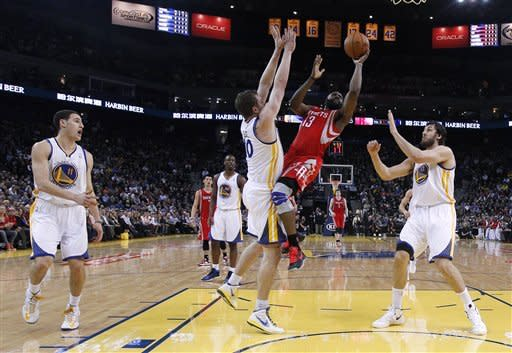 Houston Rockets' James Harden (13) shoots between Golden State Warriors' Klay Thompson (11), David Lee, center, and Andrew Bogut (12) during the first half of an NBA basketball game in Oakland, Calif., Tuesday, Feb. 12, 2013. (AP Photo/Marcio Jose Sanchez)