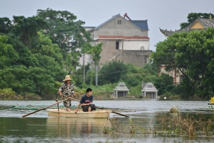 Residents take a boat in a flooded area of Poyang county in China's central Jiangxi province (AFP Photo/Hector RETAMAL)