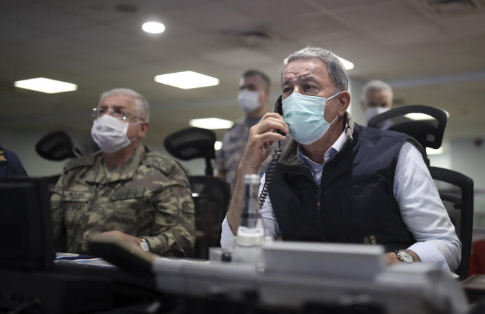 """In this photo taken Monday, June 15, 2020, Turkish Defense Minister Hulusi Akar, right, and Chief of Staff Gen. Yasar Guler wearing face masks to protect against the coronavirus, monitor the operation at a military headquarters in Ankara, Turkey. Turkey said Wednesday it has airlifted troops for a cross-border ground operation against Kurdish militants in northern Iraq. The airborne offensive in Iraq's Haftanin region, some 15 kilometers (9 miles) from the border, was launched following """"intense"""" artillery fire into the area, a Defense Ministry statement said. (Turkish Defense Ministry via AP, Pool)"""