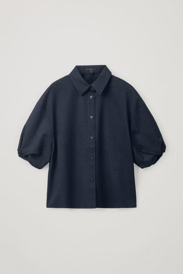 """<p>Cos Cotton Puff Sleeve Seersucker Shirt, $99, <a href=""""https://rstyle.me/+NWDrPDBlS_U1oYhYSuFVdQ"""" rel=""""nofollow noopener"""" target=""""_blank"""" data-ylk=""""slk:available here"""" class=""""link rapid-noclick-resp"""">available here</a>.</p>"""