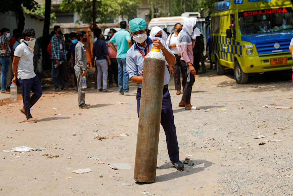 <p>File: A healthcare worker holds an oxygen cylinder outside a factory as he waits to get it refilled</p> (Reuters)