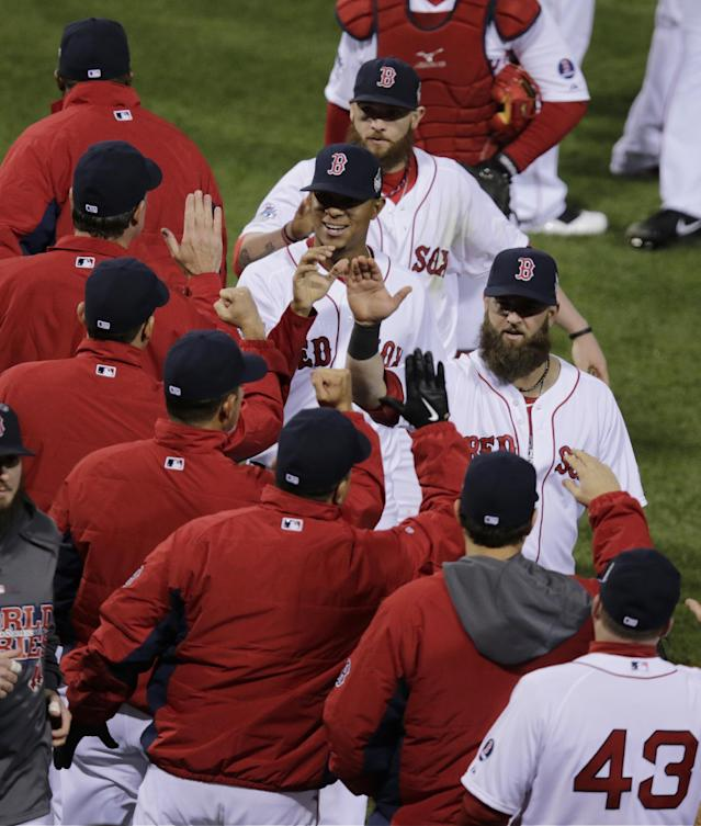 Boston Red Sox players celebrate after Game 1 of baseball's World Series against the St. Louis Cardinals Wednesday, Oct. 23, 2013, in Boston. The Red Sox won 8-1 to take a 1-0 lead in the series. (AP Photo/Charles Krupa)