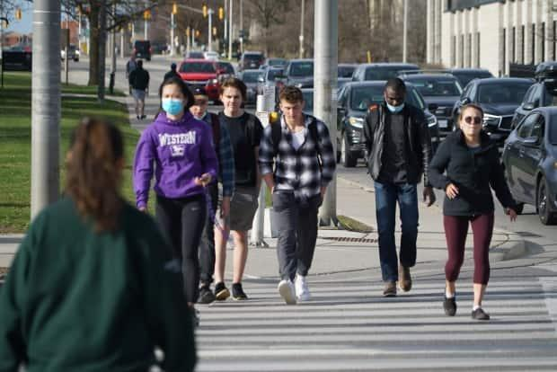 Students walk through a busy intersection on the rim of the Western University campus in London, Ont.  (Colin Butler/CBC - image credit)