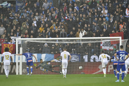 Alaves' Lucas Perez, scores a penatly as Real Madrid's goalkeeper Alphonse Areola tries to catch the ball during the Spanish La Liga soccer match between Real Madrid and Alaves at Mendizorroza stadium, in Vitoria, northern Spain, Saturday, Nov. 30, 2019. (AP Photo/Alvaro Barrientos)
