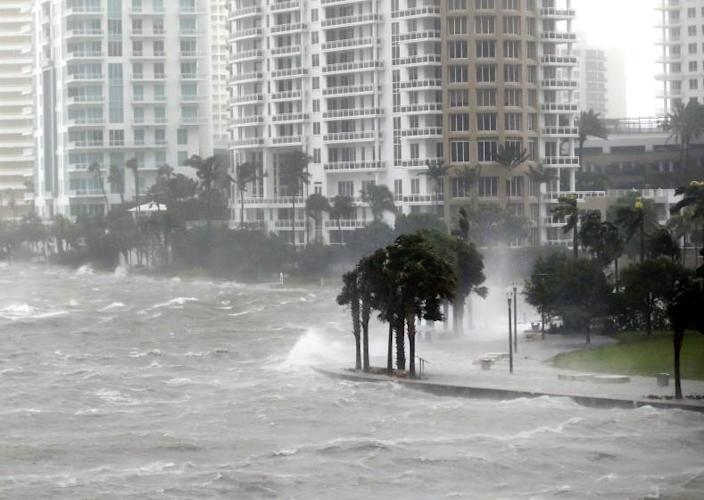 FILE - In this Sept. 10, 2017 file photo waves crash over a seawall at the mouth of the Miami River from Biscayne Bay, during Hurricane Irma, in Miami. The year's biggest news stories chronicled an historic hurricane season that had Florida in its crosshairs. Hurricane Irma knocked out power for millions across wide swaths of the state on both coasts, from Key West to Jacksonville, left homes destroyed and lives disrupted. (AP Photo/Wilfredo Lee, File)