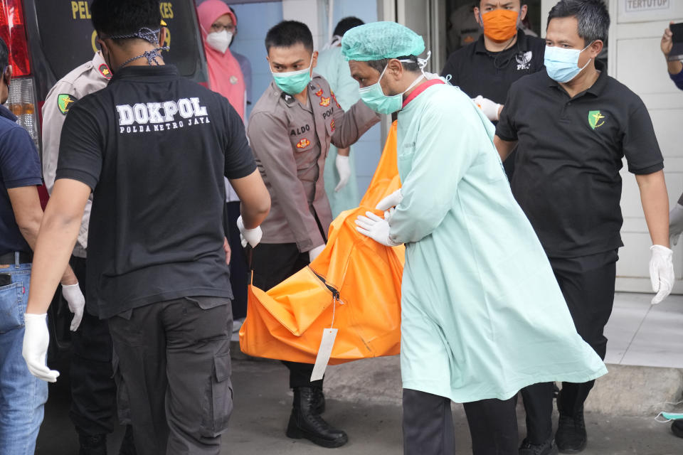 Officers load a body bag containing the body of a victim of a prison fire to be transferred to the national police hospital for identification from the local hospital in Tangerang on the outskirts of Jakarta, Indonesia, Wednesday, Sept. 8, 2021. A massive fire raged through the overcrowded prison early Wednesday, killing a number of inmates. (AP Photo/Dita Alangkara)