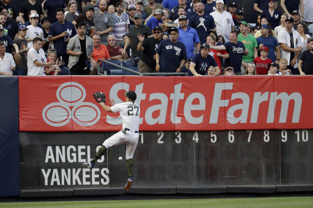 New York Yankees left fielder Giancarlo Stanton (27) prepares to hit the wall while fielding a double from Los Angeles Angels' Mike Trout during the first inning of a baseball game Saturday, May 26, 2018, in New York. (AP Photo/Julio Cortez)