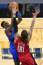 Orlando Magic guard Dwayne Bacon, left, makes a shot over Houston Rockets forward D.J. Wilson (00) during the second half of an NBA basketball game, Sunday, April 18, 2021, in Orlando, Fla. (AP Photo/John Raoux)