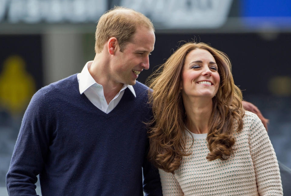 Catherine (R), Duchess of Cambridge, and her husband, Britain's Prince William, laugh as they watch a young players' rugby tournament held at Forsyth Barr Stadium in Dunedin April 13, 2014. Prince William and his wife are undertaking a 19-day official visit to New Zealand and Australia with their son, Prince George. REUTERS/David Rowland/Pool (NEW ZEALAND - Tags: SOCIETY ROYALS SPORT RUGBY TPX IMAGES OF THE DAY)