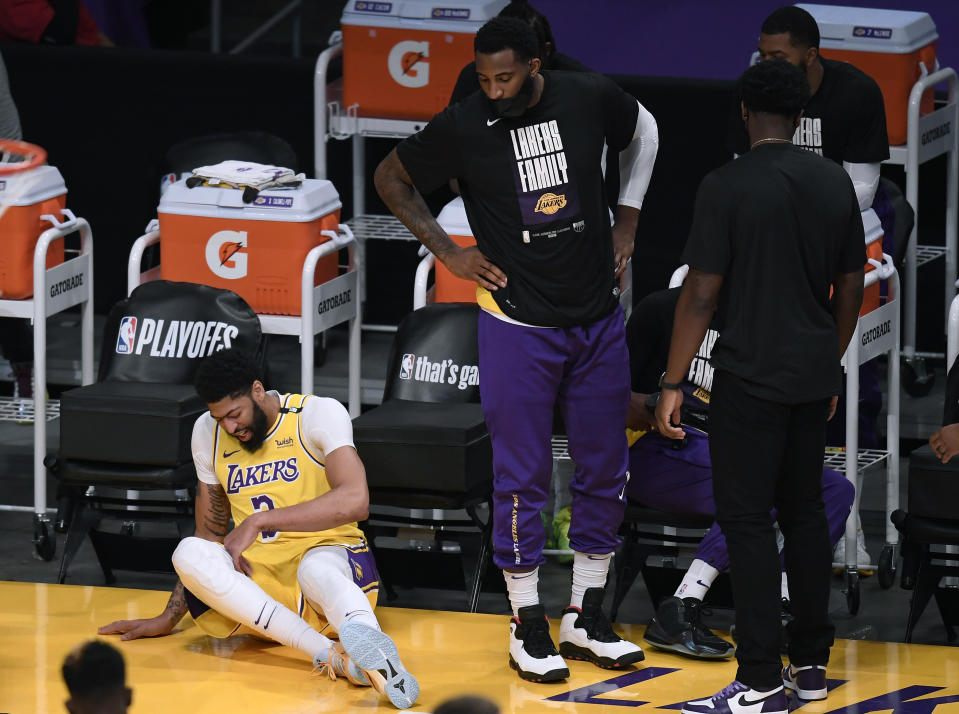 Anthony Davis of the Los Angeles Lakers falls at the Laker bench