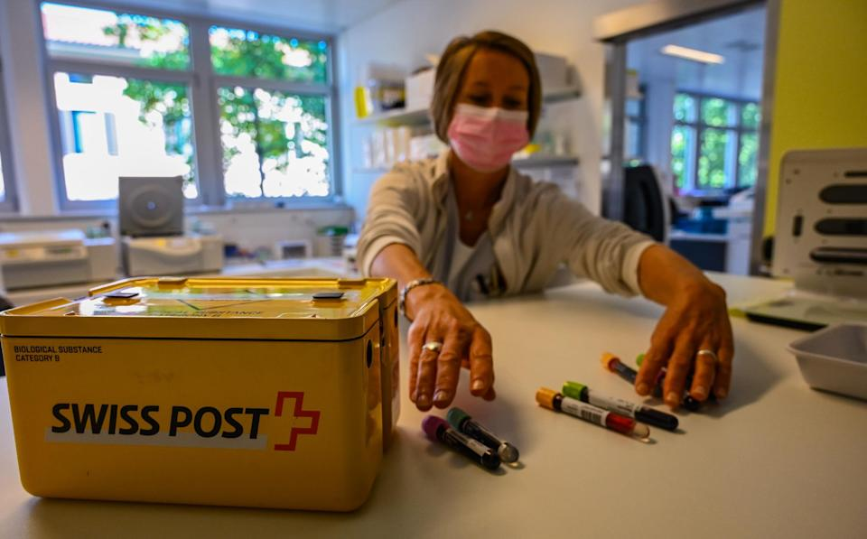 A woman sorts vials to put in a SwissPost carrier for a drone to take to another facility.