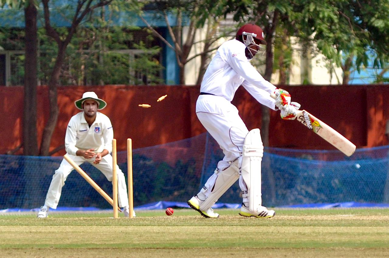 West Indies player Chris Gayle gets bowled during a practice match between Uttar Pradesh Cricket Association XI and West Indies at the Jadavpur University Ground in Kolkata on Oct.31, 2013. (Photo: IANS)