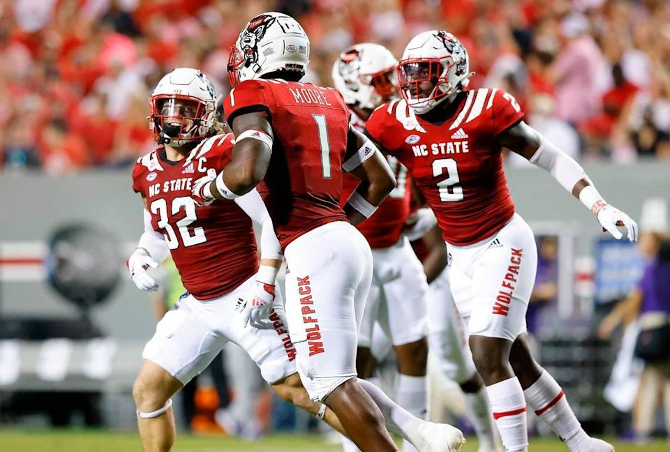 N.C. State linebacker Drake Thomas (32), Isaiah Moore (1) and Jaylon Scott (2) celebrate a stop during the first half of N.C. State's game against Furman at Carter-Finley Stadium in Raleigh, N.C., Saturday, Sept 18, 2021.