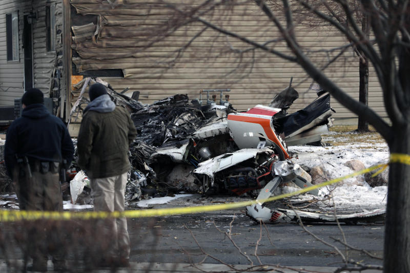 People look at the debris from a small private plane that crashed in a residential area Wednesday, Jan. 15, 2020, in Roy, Utah. The small plane crashed Wednesday, killing the pilot as the aircraft narrowly avoided hitting any townhomes, authorities said. (Ben Dorger/Standard-Examiner, via AP)