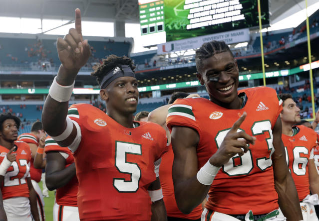 Miami quarterback N'Kosi Perry (5) and wide receiver Evidence Njoku (83) sing the alma mater after an NCAA college football game against FIU, Saturday, Sept. 22, 2018, in Miami Gardens, Fla. (AP Photo/Lynne Sladky)