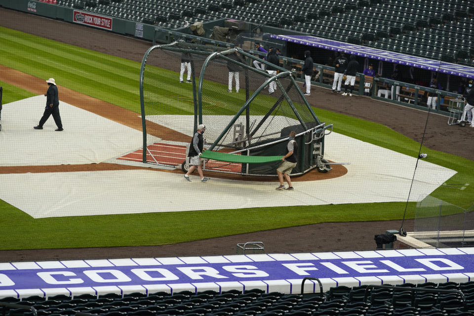 Grounds crew workers prepare to pull the tarpulin as a light rain descends on Coors Field Tuesday, April 6, 2021, before the Colorado Rockies host the Arizona Diamondbacks in a baseball game in Denver. Major League Baseball announced that Coors Field will be the venue for the 2021 All Star Game after the Midsummer Classic was moved out of Atlanta because of sweeping changes to voting rights established in the state of Georgia. (AP Photo/David Zalubowski)