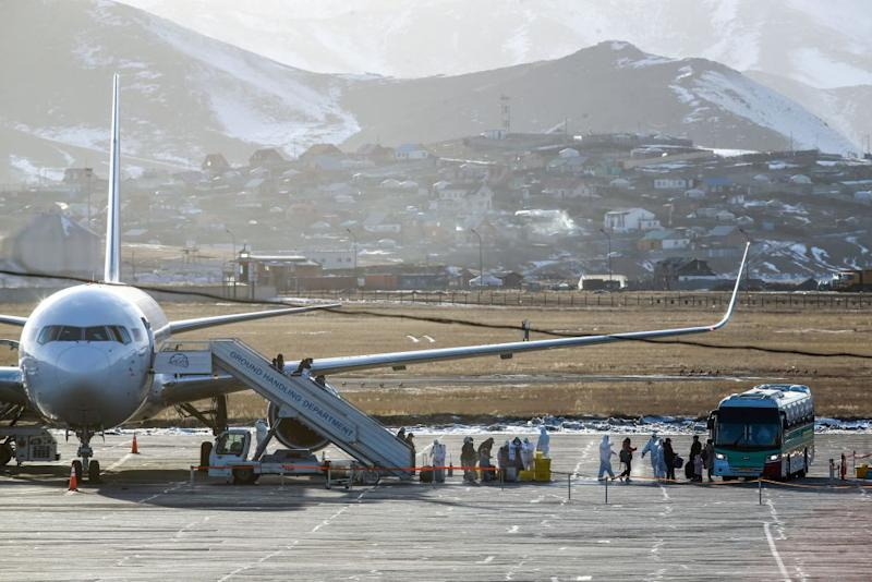 Officials in hazmat suits greet passengers on a plane against the backdrop of Mongolian capital Ulaanbaatar,.