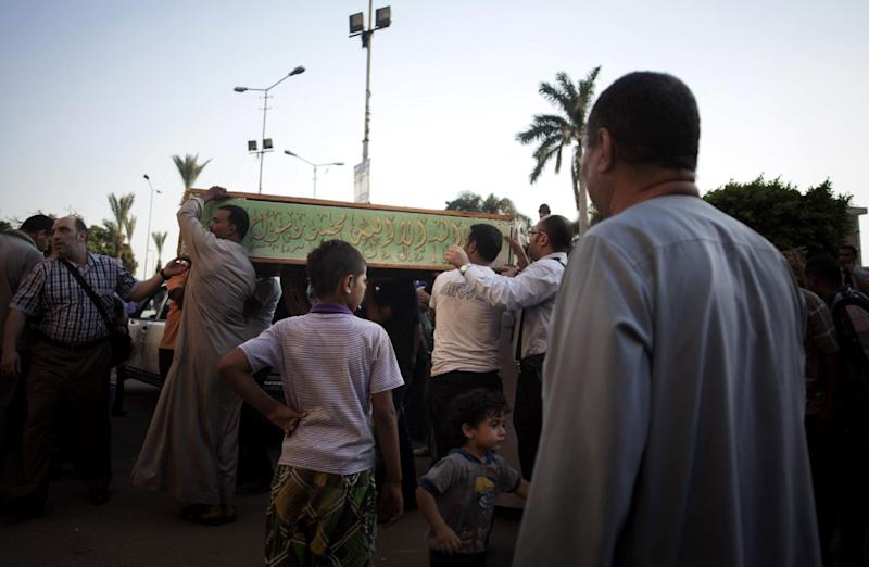 Egyptians carry the coffin of a Shiite man during the funeral procession of four Shiites outside the Sayida Nafisa mosque in Cairo, Egypt, Monday, June 24, 2013. Egypt's Islamist president condemns the killing of four Shiites by a Sunni Muslim mob that beat the men to death in their homes. But critics say he is in part to blame for implicitly supporting his hard-line allies as they stir up incitement against Shiites over Syria's civil war, and they warn that militant Islamists are acting with impunity. (AP Photo/Manu Brabo)