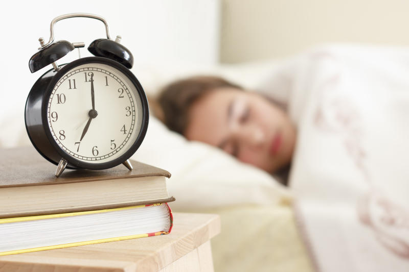 Teenager girl sleeping in a white bed. Alarm clock in the foreground on pile of books