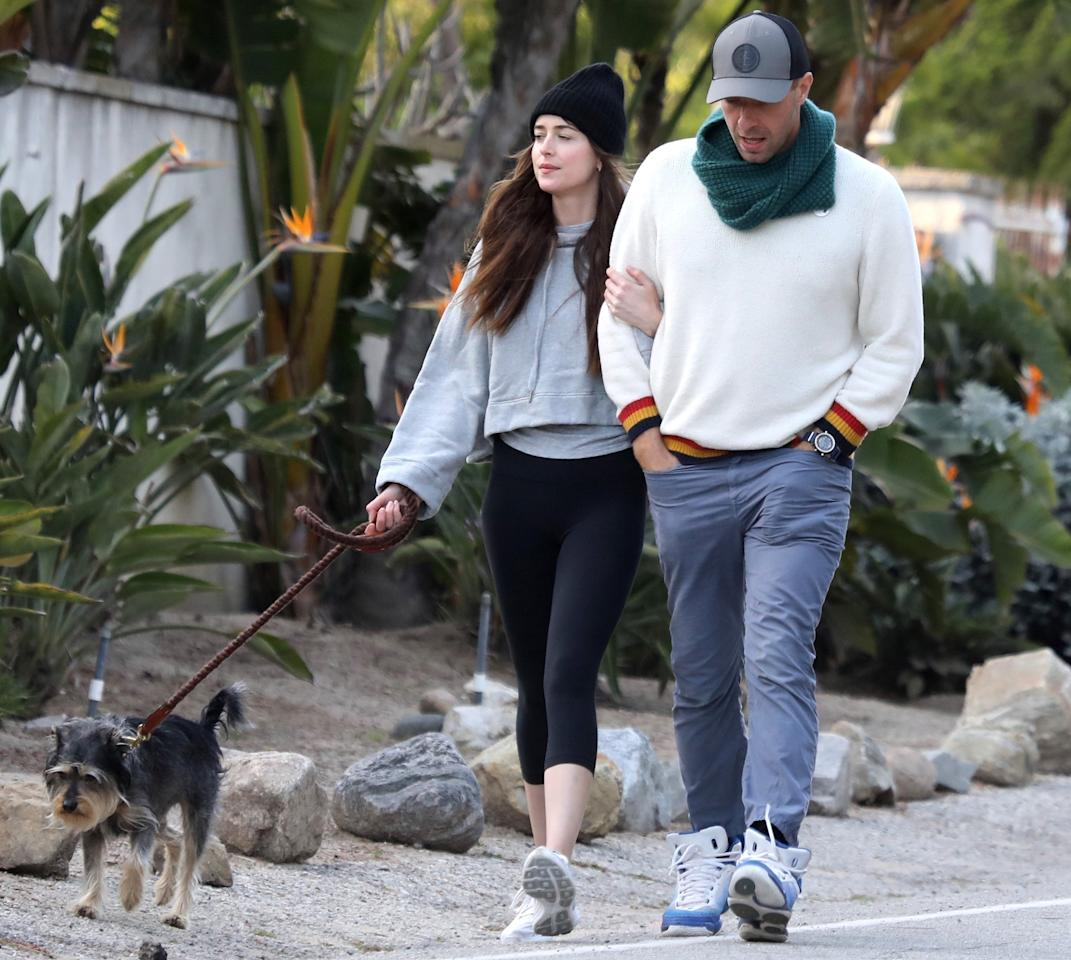 <p>Dakota Johnson and Chris Martin link arms during a walk in Malibu, California, with her dog on Saturday.</p>