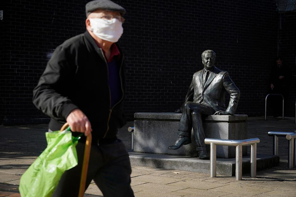 <strong>A man wearing a protective face mask walks past a statue of former prime minister Harold Wilson in Huyton in Liverpool.</strong> (Photo: Christopher Furlong via Getty Images)