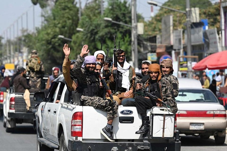 Taliban fighters wave as they patrol in a convoy along a street in Kabul on Thursday (AFP via Getty)