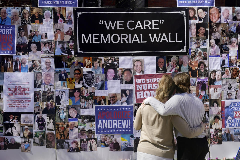 FILE - In this March 21, 2021 file photo, Theresa Sari, left, and her daughter Leila Ali look at a section of a memorial wall after a news conference in New York Sari's mother, Maria Sachse, was a nursing home resident and died from COVID-19. After a deadly year in New York's nursing homes, state lawmakers have passed legislation that could potentially force facility owners to spend more on patient care. (AP Photo/Seth Wenig)