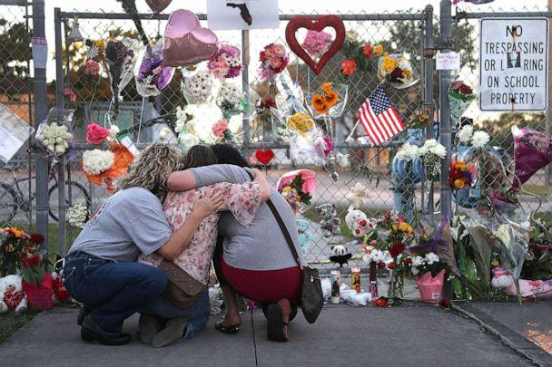 PHOTO:Shari Unger, Melissa Goldsmith and Giulianna Cerbono (L-R) hug each other as they visit a makeshift memorial setup in front of Marjory Stoneman Douglas High School, Feb. 18, 2018, in Parkland, Fla. (Joe Raedle/Getty Images)
